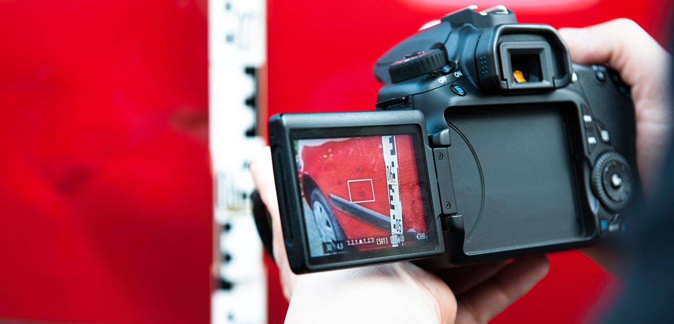 KFZ Gutachter macht Kameraufnahmen eines Autos